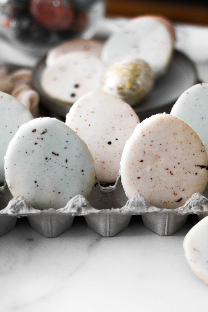 Blue and rose colored egg shaped cookies with speckles sitting in an egg carton.