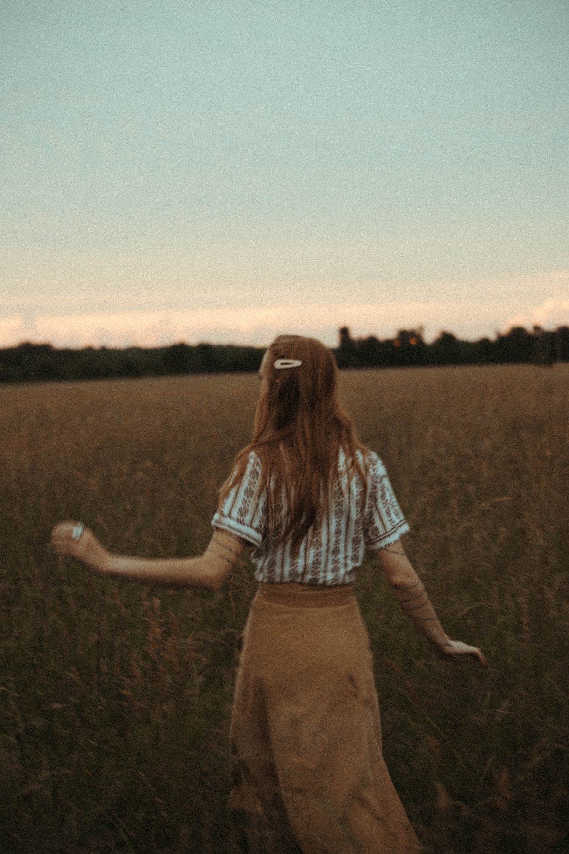 red head girl running in a field sunset moody creative photography