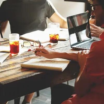 Groupe de personne autour d'une table avec un ordinateur pour la mise en avant du service de consulting pour entreprise