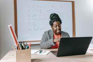 excited black teacher explaining mathematics online on laptop