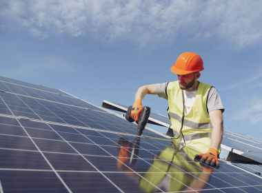 man fixing solar panels with professional drill
