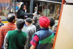 Student volunteer Aliya Bhat hands out pamphlets at the RTI-on-Wheels halt in Kupwara.