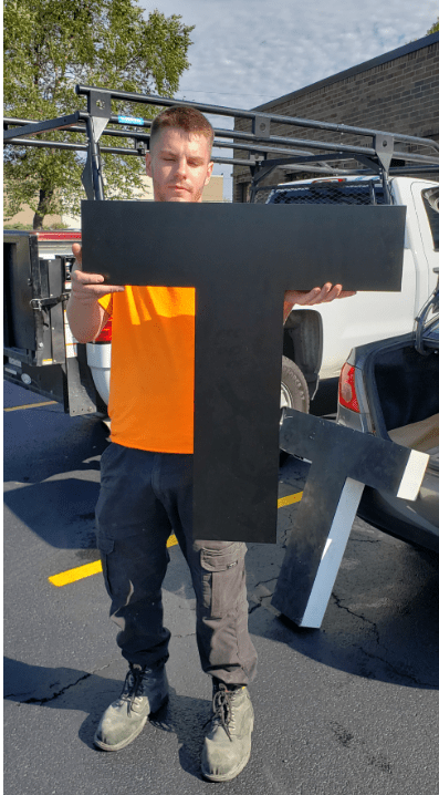 Worker holds the new letter T