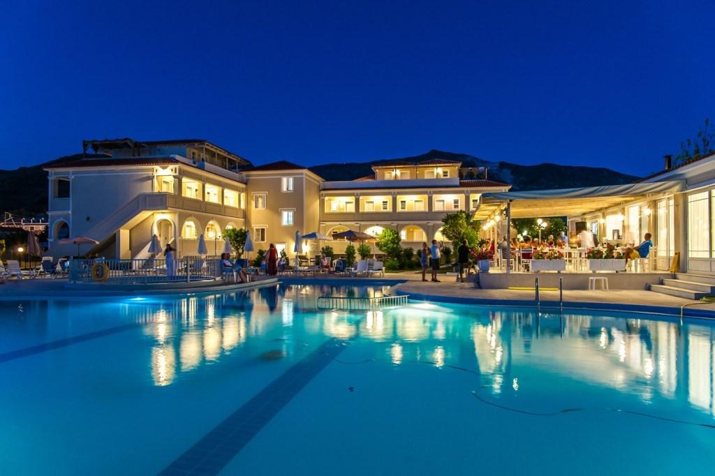 Νυχτερινή θέα του φωτισμένου ξενοδοχείου, στο οποίο φαίνεται η πισίνα και το μπαρ.