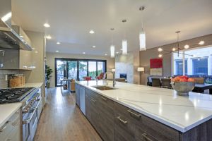 Sleek modern kitchen design with a kitchen peninsula fitted with a gray and white quartz countertop.