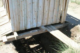 Just a few wood planks hammered together over a shallow pit.