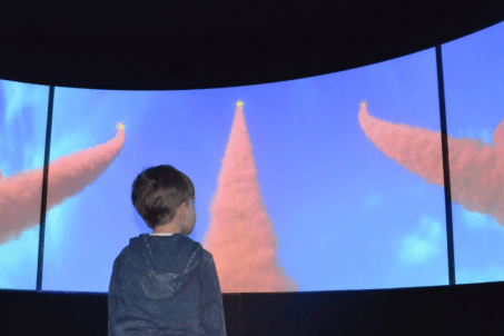 A young child stands in front of what appears to be a screen.