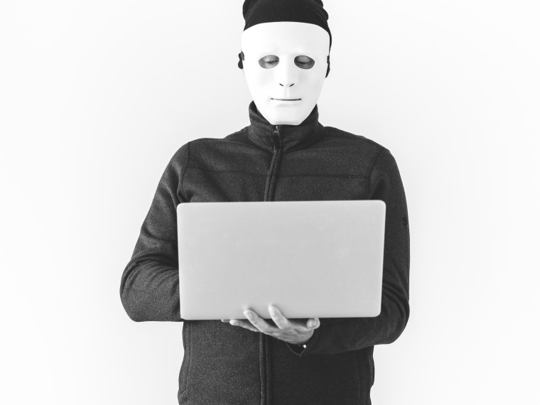 writing scams signs feature image - man in mask looking down at laptop, black and white effect.