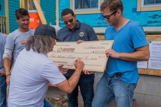"Philanthropist Brook Smith signs over a check for $300,000 to unCommon Construction. People behind the check include: Aaron Frumin, executive director of uCC; Councilmember Jared Brossett ""District D""; and Josh Schoop, board member of uCC (L – R)."