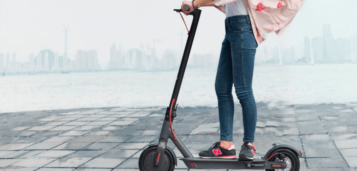 Young woman riding a Xiaomi M365 electric scooter