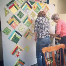 Pat and Lori playing with layout on the design walls. Loving those scrappy blocks! #svmqgretreat by siliconvalleymqg