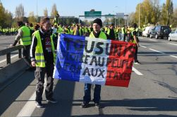 "A man holds a French flag with the inscription ""All united, glory to the people, stop taxes"" as he stands on the rocade (ring road) during a demonstration of Yellow Vests (Gilets jaunes) against the rising of the fuel and oil prices on November 17, 2018 in Bordeaux, southwestern France. - Thousands of drivers blocked roads across France in a ""yellow vest"" movement against high fuel prices which has mushroomed into a widespread protest against stagnant spending power under French President. (Photo by NICOLAS TUCAT / AFP) (Photo credit should read NICOLAS TUCAT/AFP/Getty Images)"