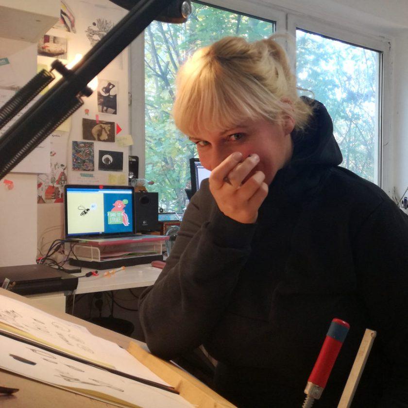 Portrait Silke Müller, Illustratorin in Linz, sie sitzt am Zeichentisch im Atelier, hat einen Pinsel zwischen den Fingern und lacht, Editorial Illustration