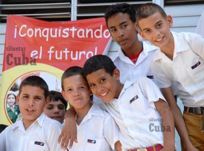 """Estudiantes de la Escuela Secundaria """"Mártires de Regla"""" posan detrás de un cartel que dice """"Conquistando el futuro"""", previo al VI Congreso pioneril, el 8 de Marzo de 2011, La Habana, Cuba. Foto: Calixto N. Llanes/Juventud Rebelde (CUBA)"""