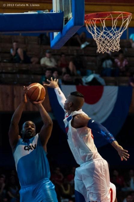 Yoan Luis Haiti (izquierda) de Ciego de Ávila, tira al aro ante la defensa de Jasiel Rivero (14) de Capitalinos, durante el segundo juego de la final de la Liga Superior de Baloncesto (LSB). El duelo celebrado en el Coliseo de la Ciudad Deportiva terminó 71-50 favorable a Ciego, el viernes 13 diciembre de 2013, La Habana. FOTO de Calixto N. Llanes (CUBA)