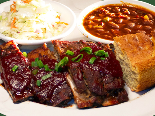 Photo of BBQ pork ribs served with coleslaw, beans, and bread