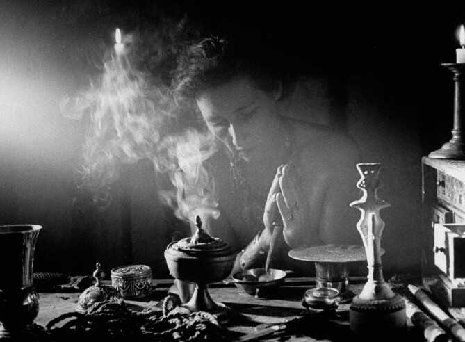"""La suma sacerdotisa Artemisa remueve una mezcla de sal y agua que es usada para """"purificar"""" el círculo en todos los ritos de brujería. En la mesa hay un incensario, una cuerda y una estatua de la diosa. A la derecha un baúl de hierbas que contiene incienso."""