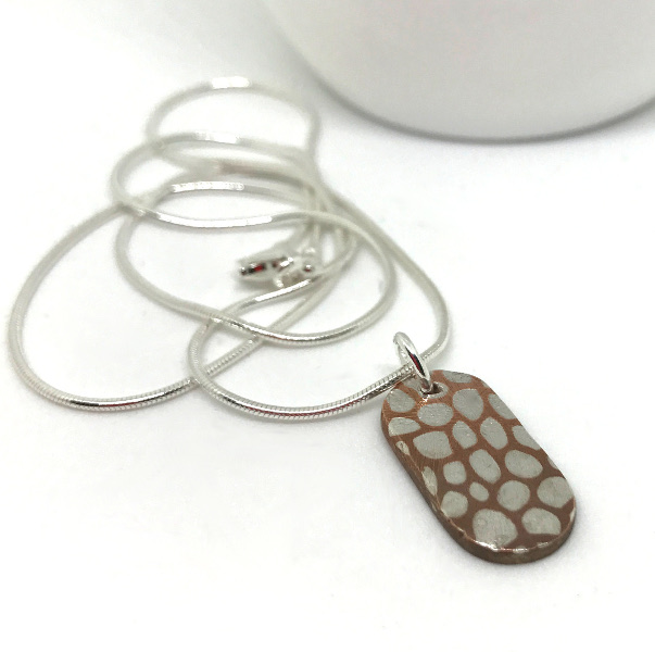 Silver inlay to copper pendant
