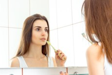 young woman brushes teeth