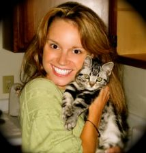 Image of Young woman in green shirt hugs American Shorthair silver tabby kitten