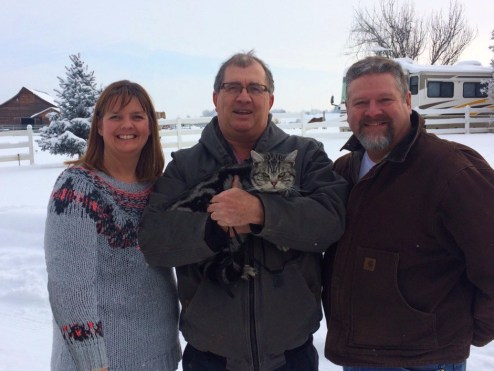 Image of three people holding American Shorthair silver tabby cat on snowy day