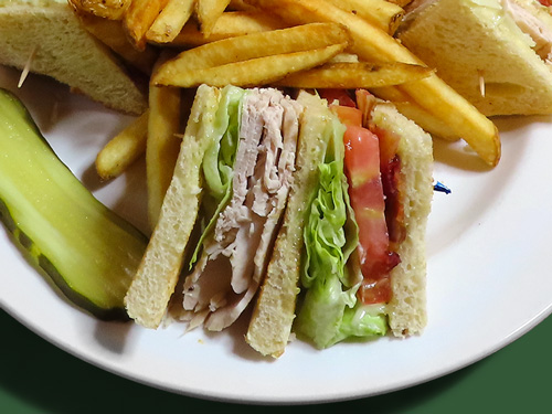 Photo of turkey clubhouse sandwich served with a pickle slice and pile of fries