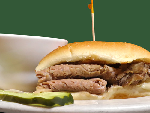 Photo of french dip sandwich served with au jus and a pickle slice