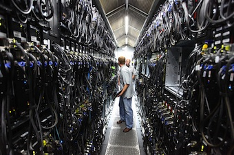 Two people talking to one another in a data center hallway about one person wide with bunches of racks and cabling on either side