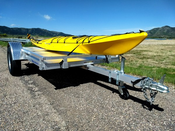 yellow kayak being towed by the trailer