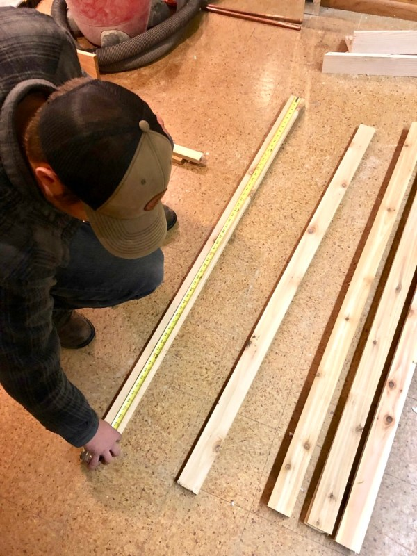 Josh measuring the length of board to cut