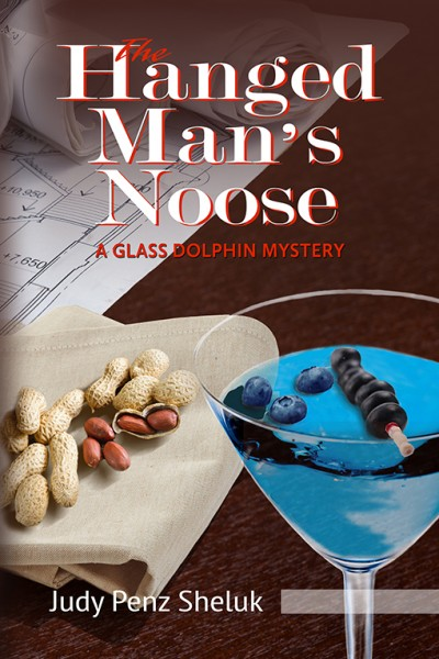"Cover of the book ""The Hanged Man's Noose"" by Judy Penz Sheluk, featuring blueprints, peanuts on a napkin and a blueberry martini"