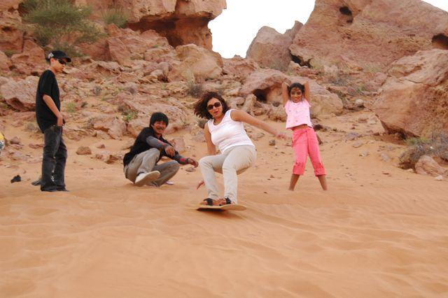 Naznin, Arif's high school sweetheart, taking on a sandboarding challenge on a desert dune in Dubai