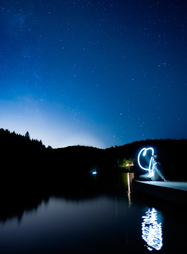 Astrophotography of a lake with stars and light art in the foreground
