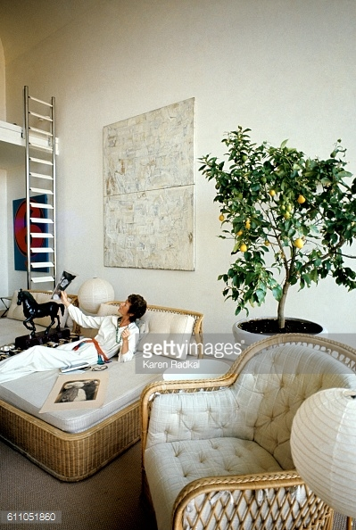 Marella Agnelli in her living room looking at a photographs by Cameron *** Local Caption ***