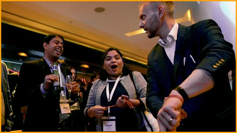 Magician at corporate event performs close up magic to two gasping spectators.