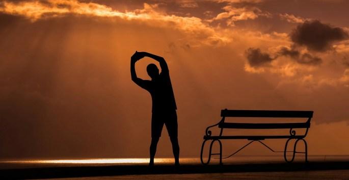 uomo che sta facendo riscaldamento per la corsa al tramonto con a fianco una panchina