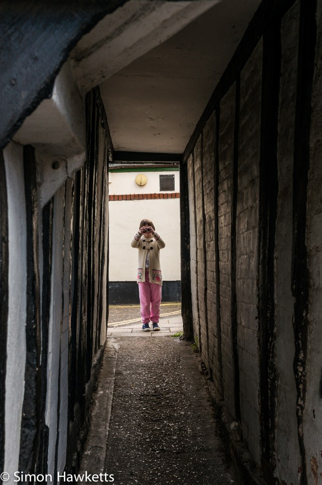 Pictures of Framlingham in Suffolk - A girl with a camera viewed through an alleyway