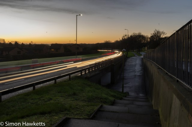 A picture of a busy road in the early morning with long trails formed by the car lights