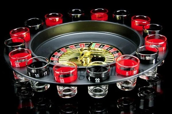 The picture depicts a Roulette wheel. However, this is not just an ordinary Roulette wheel. Apart from being a functional gambling device, this is also a prop for a drinking game. There are black and red numbered shoot glasses around the Roulette wheel. After spinning the Roulette wheel participants must drink from the corresponding shot glass. Under the picture you can see different roulette games, which you can play for free. Click on any of the different types to start winning money.