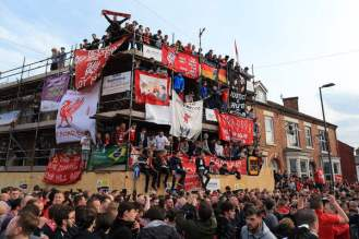 Liverpool fans climb on scaffold to welcome the team bus before their side's UEFA Europa League Semi-Final (2nd Leg) match against Villarreal