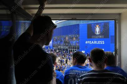 Leicester fans enjoy a beer as they look out over the King Power Stadium from their hotel room