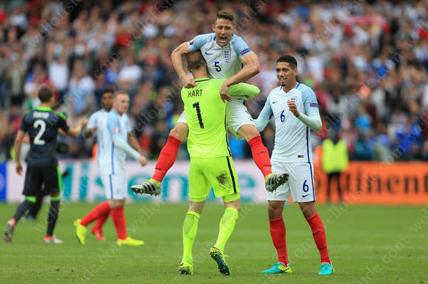 Gary Cahill of England jumpsinto the arms of teammate England goalkeeper Joe Hart alongside Chris Smalling of England as he celebrates victory