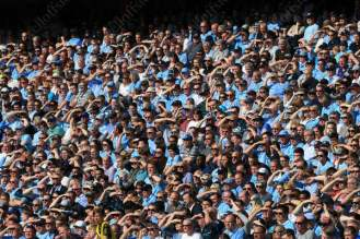 Man City fans shield their eyes from the sun during their side's match against Arsenal