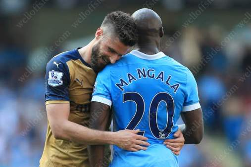 Olivier Giroud of Arsenal rests his head on the shoulder of Eliaquim Mangala of Man City