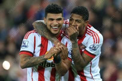 DeAndre Yedlin of Sunderland (L) and teammate Patrick van Aanholt share a joke as they celebrate after the match
