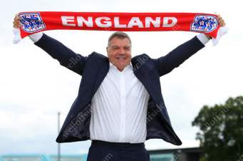 New England manager Sam Allardyce holds his country's scarf aloft