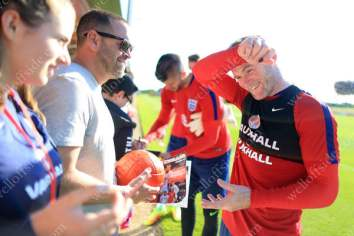 England captain Wayne Rooney wipes his brow as he signs autographs after a training session in the summer heat