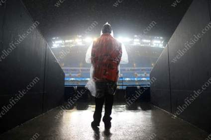 A steward wearing a poncho watches the rain come pelting down at the Etihad Stadium