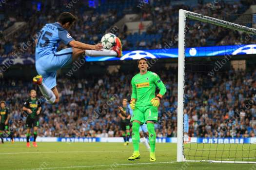 Monchengladbach goalkeeper Yann Sommer watches as Jesus Navas of Man City controls the ball in mid-air on the byline