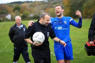 A Brixham player walks off at half-time smiling and joking with the referee